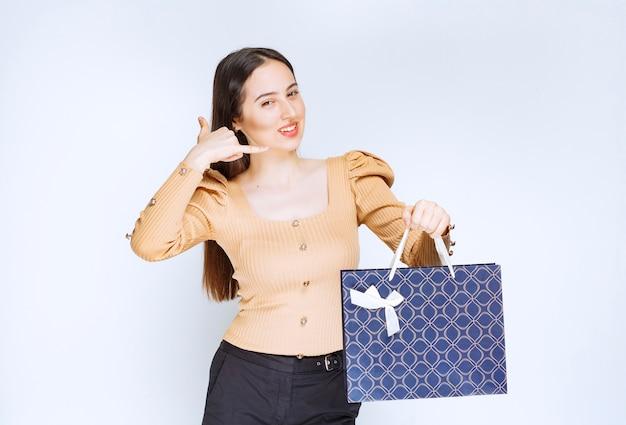 Модель красивой женщины с хозяйственной сумкой, делая жест телефонного звонка.
