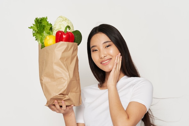 Красивая женщина азиатской внешности - пакет здорового питания
