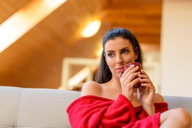 Красивая женщина на диване, завернувшись в одеяло и наслаждаясь чашкой чая