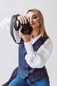 デニムのカジュアルな服装と、カメラを手にしたボリュームのある袖の白いブラウスを着た美しい女性写真家。趣味。ソフトセレクティブフォーカス。