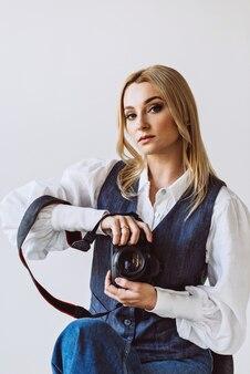 데님 캐주얼 복장의 아름다운 여성 사진 작가와 그녀의 손에 카메라가 달린 방대한 소매가 달린 흰색 블라우스. 취미. 소프트 선택적 초점.