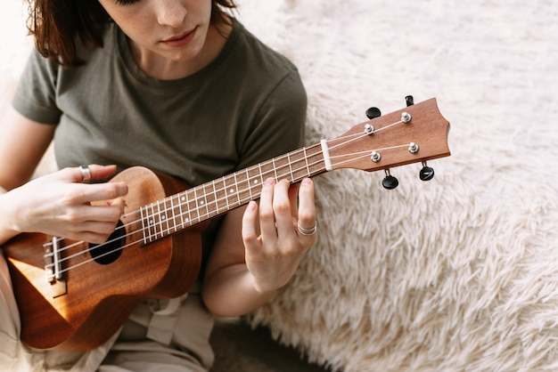 美しい女性が家で小さなギターを弾きます。若い女の子が自己隔離中にウクレレを演奏する