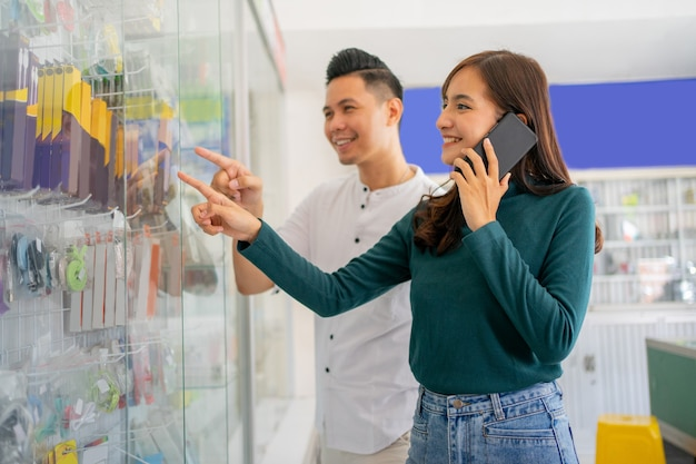 Красивая женщина, указывая на стеклянную витрину, выбирая аксессуары для мобильного телефона