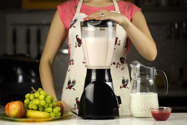 부엌에서 과일과 함께 우유 칵테일을 준비하는 아름다운 여자 프리미엄 사진
