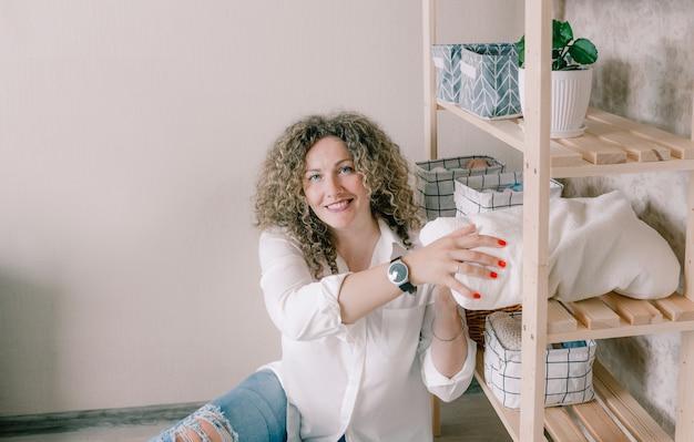 아름다운 여성은 옷장에 물건을 정리하고 물건을 제자리에 놓습니다. 집안의 질서와 편안함