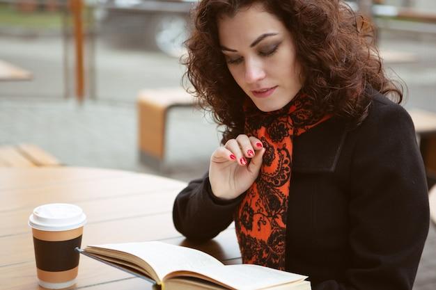 美しい女性がストリートカフェのテラスで温かい飲み物を飲みながら本を読む