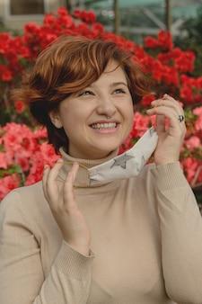 Красивая женщина снимает защитную маску и вдыхает среди весенних цветов. конец концепции пандемии коронавируса