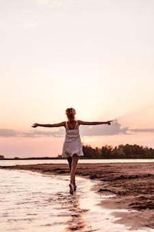 Красивая женщина бежит по пляжу вид сзади стройной молодой блондинки в белом платье на р ...