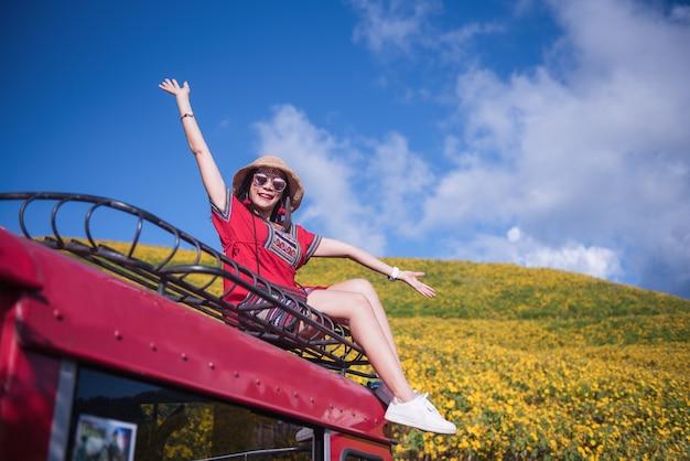 Красивая женщина сидит на крыше красной машины