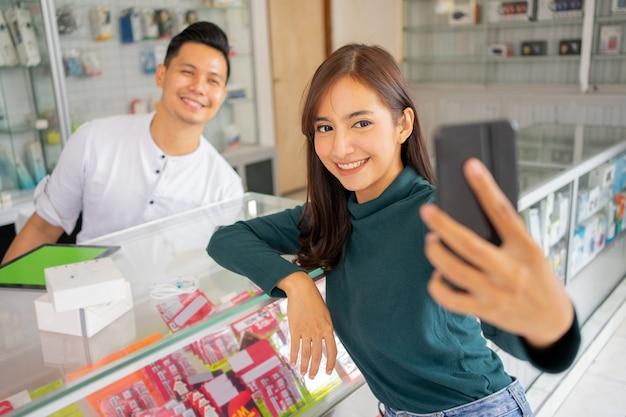 한 아름다운 여성이 근처에 앉아 있는 남자와 함께 휴대폰으로 셀카를 찍으며 미소를 짓고 있다.