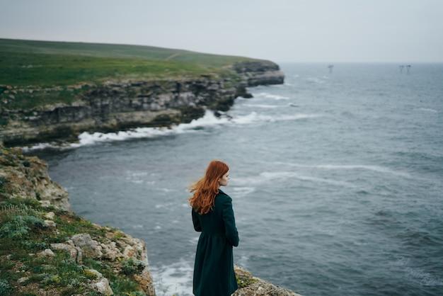 Красивая женщина стоит на скале и смотрит на океан