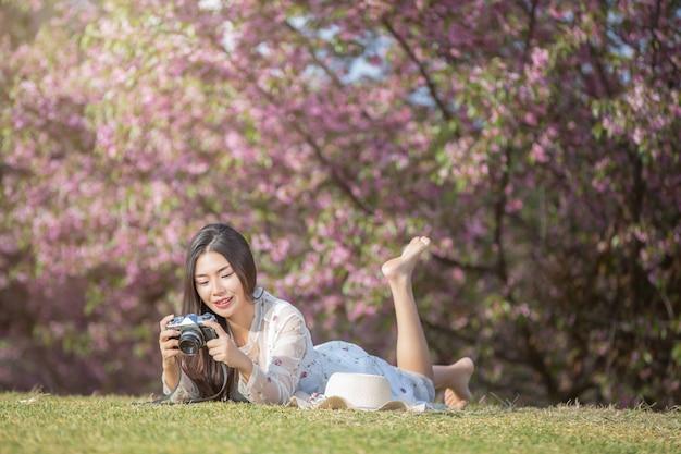 Красивая женщина фотографирует с пленочной камерой в цветочном саду сакура.