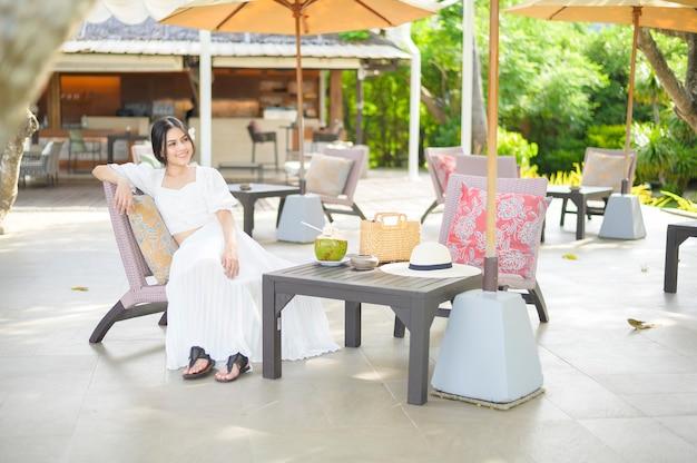 여름 방학 동안 라운지 의자에 앉아 코코넛을 마시는 그녀의 머리에 흰 꽃과 아름다운 여자 관광