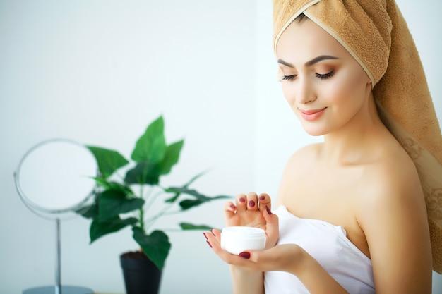 スキンケア製品、保湿剤またはローションを使用し、乾燥肌の世話をするスキンケアを使用している美しい女性。女性の手に保湿クリーム