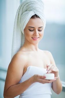 彼女の乾燥肌の世話をしているスキンケア製品、保湿剤またはローションとスキンケアを使用している美しい女性。女性の手に保湿クリーム