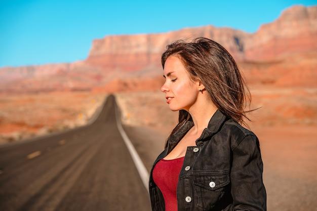 아름다운 여성은 붉은 바위가 보이는 아리조나 사막의 빈 길을 따라 걷는다