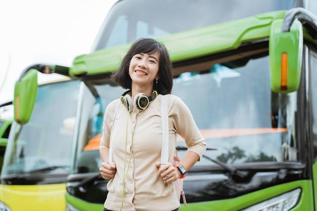 배낭과 헤드폰을 착용하는 아름다운 여자가 버스의 배경에 미소