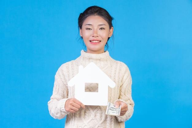 Красивая женщина, носить новый с длинными рукавами белый ковер, который держит символ дома и долларовых купюр на синем. торговая