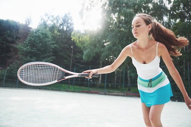 Красивая женщина, носить теннисный мяч спортивной одежды.