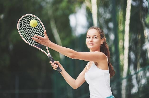 Красивая женщина носить спортивную одежду теннисный мяч.