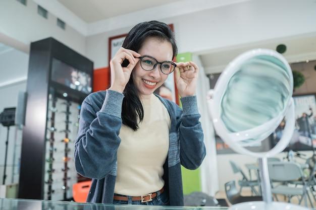眼鏡のショーウィンドウの背景を持つ眼科クリニックで選択された眼鏡をかけている美しい女性