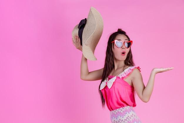 ピンクの大きな帽子と赤いメガネをかけている美しい女性。