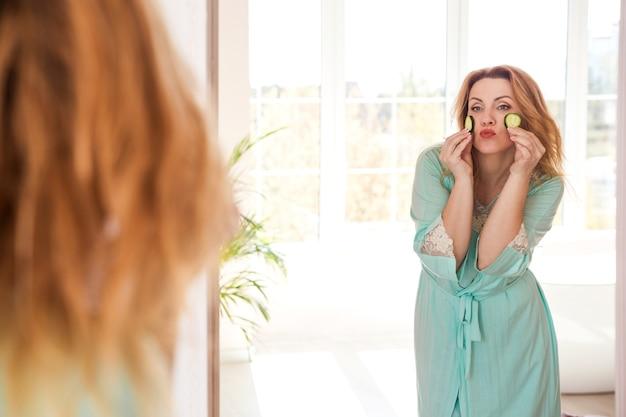 Перед зеркалом стоит красивая женщина с халатом и дольками огурца на лице.