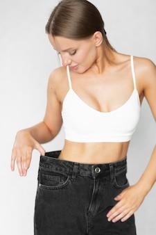 Красивая женщина с отличной фигурой в джинсах показывает, насколько она похудела