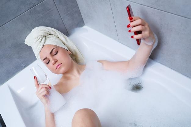 머리에 수건을 두른 아름다운 여성이 하얀 욕조에 샴페인 한 잔을 들고 누워 셀카를 찍고 있다. 힘든 하루를 보낸 후 휴식을 취하세요. 편안한 스파 트리트먼트