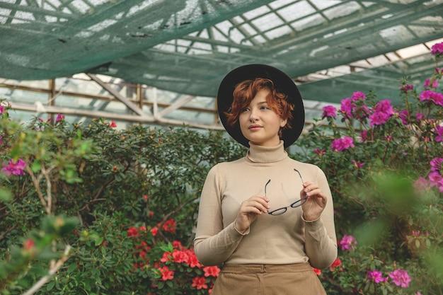 안경 및 모자 녹색 식물과 꽃 가운데 웃는 아름다운 여자.