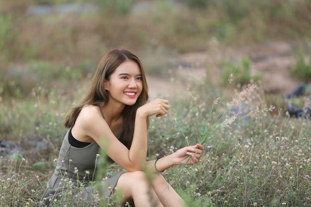 저녁 빛에 풀밭과 꽃에 앉아 드레스에 긴 머리를 가진 아름 다운 여자.