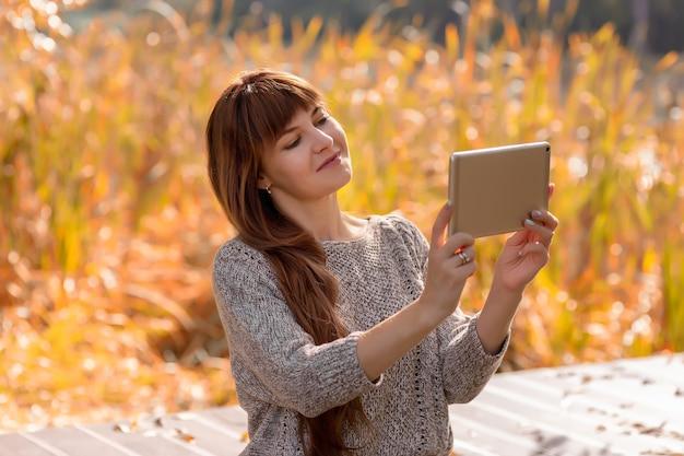 長い髪の美しい女性が屋外の秋の公園に座って、デジタルタブレットを使用してインターネット上で通信します。