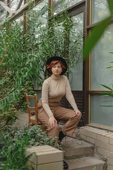 열대 식물의 녹색 가지 사이에 붉은 머리를 가진 아름다운 여인