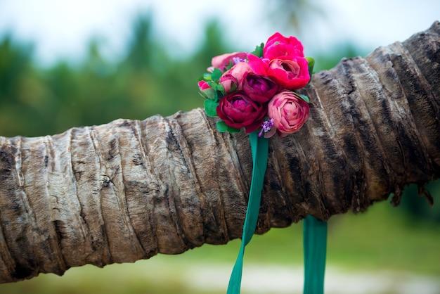 На пальме лежит красивый венок из цветов.
