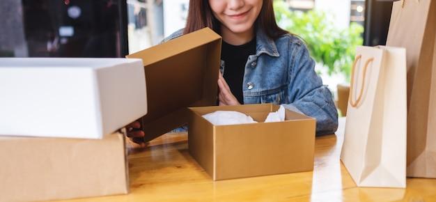 Красивая молодая азиатская женщина получая и раскрывая коробку почтовой посылки и хозяйственные сумки дома для поставки и концепции покупок онлайн