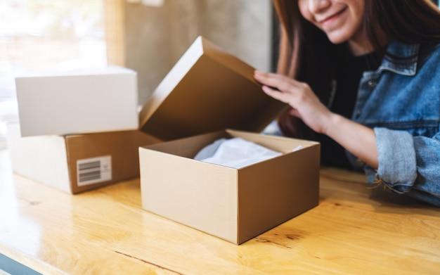 配達とオンラインショッピングの概念のために自宅で郵便小包を受け取って開く美しい若いアジア女性