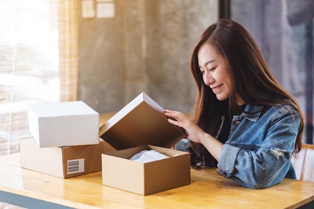Красивая молодая азиатская женщина получая и раскрывая коробку почтовой посылки дома для поставки и онлайн концепции покупок
