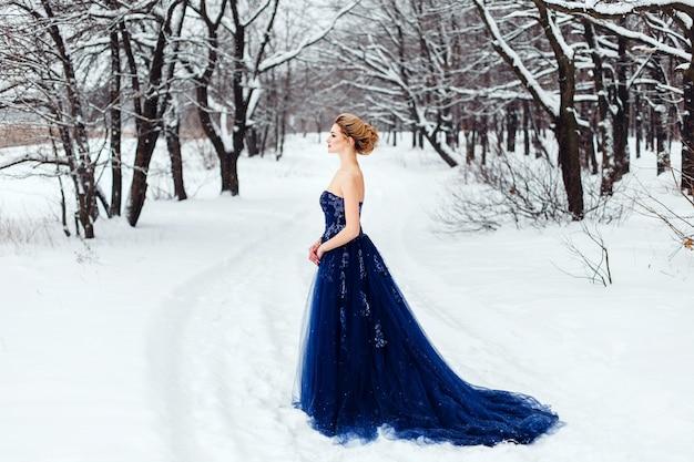 雪に覆われた冬の公園でポーズをとって青々とした青いドレスを着た美しい若いブロンドの女性