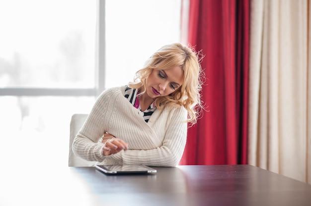 Красивая молодая блондинка женщина сидит за столом с помощью ноутбука