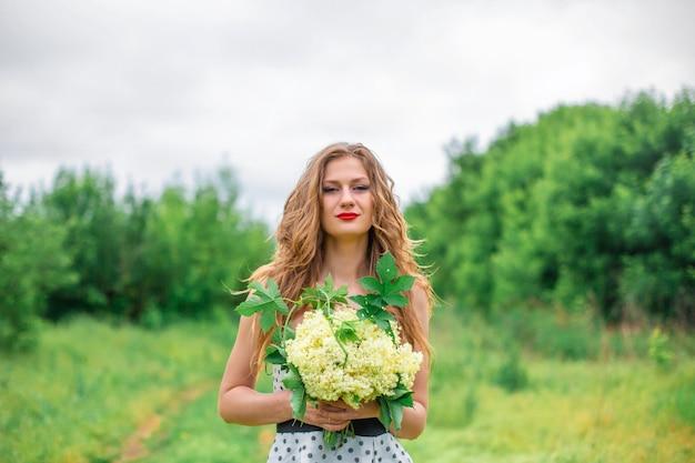 美しい若いブロンドの女の子が野花の花束を集めました。暖かい夏の日に散歩をお楽しみください。