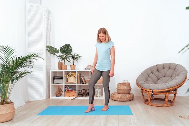 Красивая молодая блондинка катает массажный мяч вдоль ступни, выполняет гимнастические упражнения дома. со свободным пространством для текста