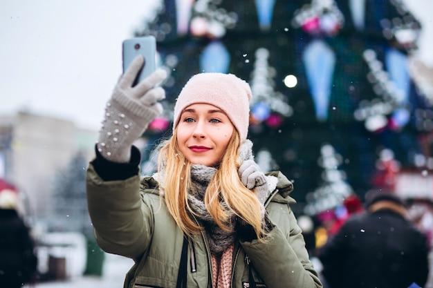 Красивая молодая блондинка улыбается в телефон, чтобы сфотографироваться на рождественской ярмарке
