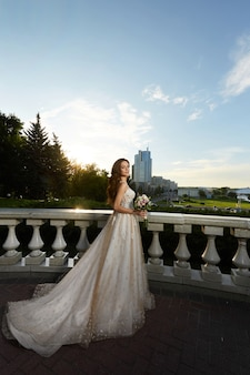 Красивая молодая невеста в роскошном кружевном свадебном платье позирует на открытом воздухе в романтическом портрете ...