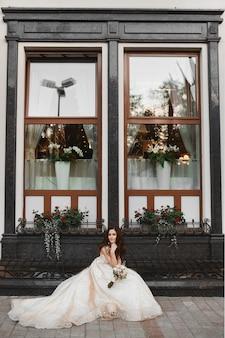 Красивая молодая невеста в роскошном кружевном свадебном платье позирует с букетом невесты на открытом воздухе ...
