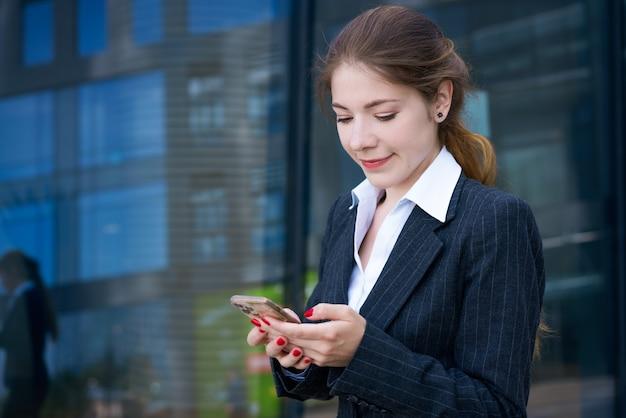 晴れた日に彼女の手に電話をして事務所ビルの背景に立っているシャツとジャケットの美しい若いブルネットの少女