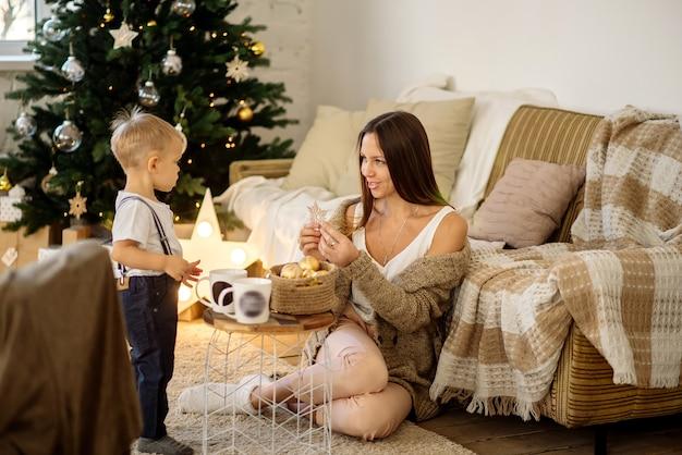 美しい若いブルネットの母親と明るい部屋で金の装飾が施された美しいクリスマスツリーで1.5歳の男の子
