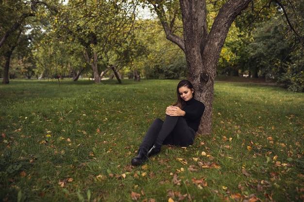 Красивая молодая брюнетка гуляет по осеннему парку в черном свитере и пальто