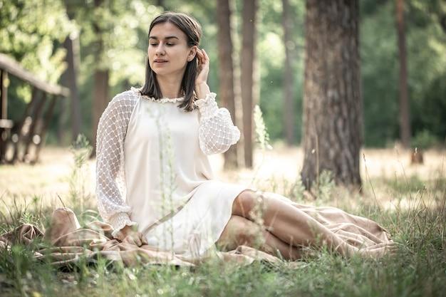 하얀 드레스를 입은 아름다운 젊은 브루네트 여성이 흐릿한 배경, 복사 공간에 있는 숲의 풀밭에 앉아 있습니다.