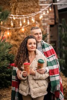 Красивая молодая пара в белых одеждах сидит возле елки в саду. счастливый мужчина и женщина, романтика, празднование рождества, веселье, любовь.