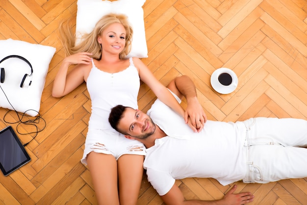 Красивая молодая пара на полу в своем новом доме с цифровыми устройствами.